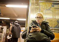 A woman listens to music near an open door on the subway in New York on Friday, December 9, 2011. A report issued by the NYPD details that half of the nearly 16,000 robberies in the city between January and October involved electronics, mostly cell phones. (© Richard B. Levine)