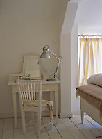 A simple wooden dressing table and chair in the corner of an attic bedroom