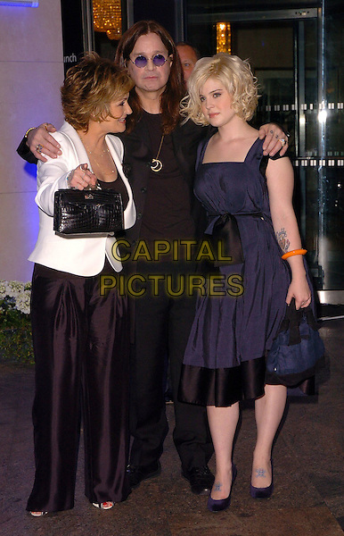 SHARON OSBOURNE, OZZY OSBOURNE & KELLY OSBOURNE.At the O2 Silver Clef Awards, Hilton Park Lane, London, Englnd, June 16th 2006..full length family mother father daughter parents navy blue dress black white jacket orange bracelet tattoo ankles feet tattoes.Ref: CAN.www.capitalpictures.com.sales@capitalpictures.com.©Can Nguyen/Capital Pictures