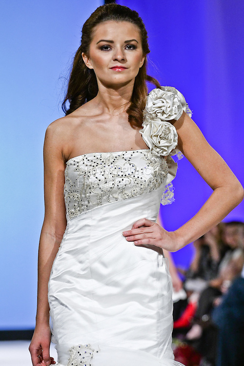 Model walks the runway in La Regina by Katerina Bocci. Duchess silk fitted gown with embellished lace. The dropped waistline leads to a two-tiered skirt. The bodice is pleated with a tulle overly & corset style back. This gown is adorned with handmade silk flowers on one sleeve as well as the skirt. During the Wedding Trendspot Press Fashion Show at the Waldorf-Astoria; October 18 2009