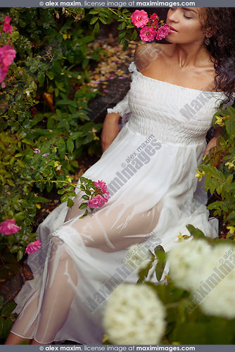 Romantic sensual portrait of a sexy young woman in wet white summer dress smelling roses lying on stairs in a garden