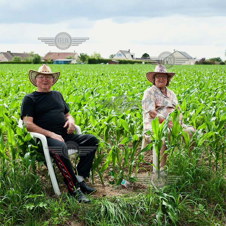 An elderly couple sit in a field of maize growing at the roadside as they wait for the riders of the Tour de France to pass by.