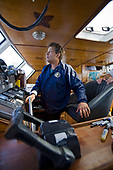"""Captain Charlie Moore at the helm of the ORV (Ocean Research Vessel) Alguita. On Sunday June 1, the raft named """"Junk""""  left Long Beach for it's 2100 mile voyage to Hawaii to bring attention to the plastic marine debris (nicknamed the plastic soup) accumulating in the North Pacific Gyre. The raft was designed and will be sailed by Dr. Marcus Eriksen of the Algalita Marine Research Foundation, and Joel Paschal, it is constructed from 15,000 plastic bottles, an airplane fuselage, discarded fishing nets and a solar generator. The raft was towed for two and a half days to near San Nicholas Island, about 65 mile of the coast of California, so it could catch favorable winds for it's trip. The tow boat was the ORV Alguita, captained by Charlie Moore of the Algalita Marine Research Foundation, the man credited for first discovering the plastic soup in the Gyre over 12 years ago."""