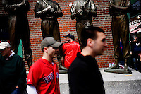 """Opening day crowds congregate around a statue entitled """"Teammates"""" by Antonio Tobias Mendez featuring the likenesses Ted Williams, Johnny Pesky, Bobby Doerr and Dom DiMaggio, stands outside of Gate B at Fenway Park in Boston, Massachusetts, USA."""