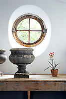 "In front of a reclaimed ""oeil de boeuf"" window are a pair of 19th century stone jardinieres on a potting table"