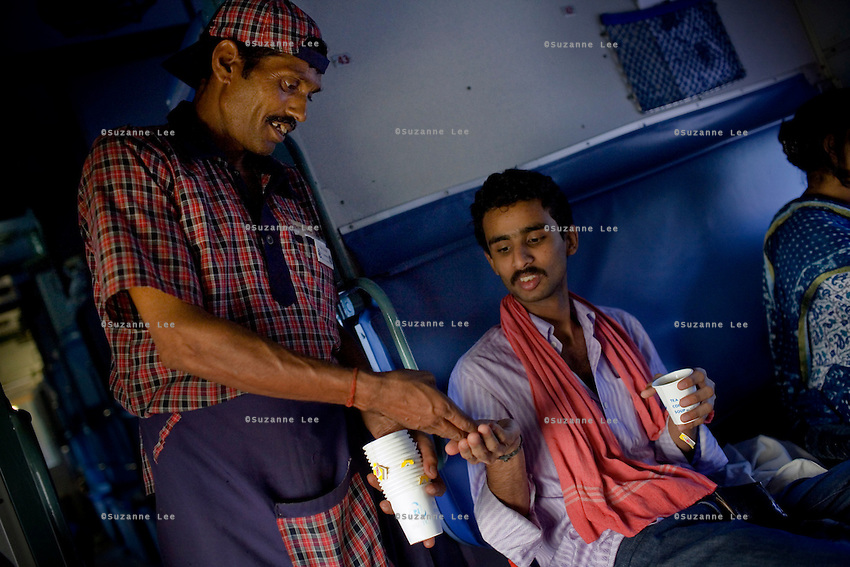 L-R.Ram Kumar, a waiter who works 6 and a half days a week on board the Himsagar Express..sells chai to.Sreenath K.B. aged 23, is a biochemistry graduate currently working as an AIDS Researcher with the National Institute of Immunology (NII) is going from Delhi to Cochin to visit his family..---------.Train passengers on the Himsagar Express 6318 going from Jammu Tawi station to Kanyakumari on 8th July 2009.. .6318 / Himsagar Express, India's longest single train journey, spanning 3720 kms, going from the mountains (Hima) to the seas (Sagar), from Jammu and Kashmir state of the Indian Himalayas to Kanyakumari, which is the southern most tip of India...Photo by Suzanne Lee / for The National