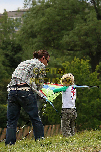 GAVIN ROSSDALE & KINGSTON ROSSDALE .Out in Primrose Hill with their family in London, England, UK, May 8th 2011..full length flying kite father dad son child kid green plaid shirt jeans back rear behind .CAP/HIL.©John Hillcoat/Capital Pictures.