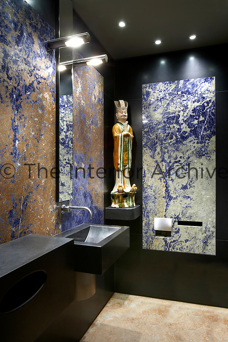 With his clients' collection of Asian art in mind, California-based designer Ron Mann refurbished a modern penthouse in London overlooking the Thames. A proud statue takes pride of place in a blue and black bathroom composed of natural materials.