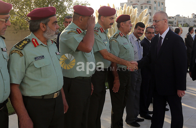Palestinian Prime Minister Rami Hamdallah shakes hands with Palestinian officers on the first day of Eid al-Adha, in the West Bank city of Ramallah on September 24, 2015. Muslims across the world are celebrating the annual festival of Eid al-Adha, or the Festival of Sacrifice, which marks the end of the Hajj pilgrimage to Mecca and in commemoration of Prophet Abraham's readiness to sacrifice his son to show obedience to God. Photo by Prime Minister Office