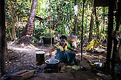A village woman cooks in the outdoor kitchen of her house in Kwin Sekhan Village in Pyapon district of Myanmar.