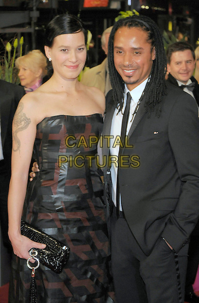 "FRANKA POTENTE & VERLOBTER DIO.Arrivals for the opening film ""The .International "", Berlinale 2009, 59th International Film Festival, Berlin, Germany..February 5th, 2009.half length strapless brown black print tattoo dreadlocks clutch bag dress suit tie .CAP/PPG/JH.©Jens Hartmann/People Picture/Capital Pictures"