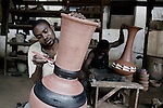 ACCRA, GHANA - JUNE 13: A worker paints a vase at Unique Ceramics Center factory on June 13, central Accra, Ghana. The company hopes to increase its domestic and export business by working with Herman Chinery-Hesse, a local software entrepreneur, who is pioneering to bringing e-commerce to remote corners of the continent. (Photo by Per-Anders Pettersson).....