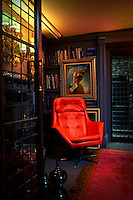 A red leather chair provides a vibrant splash of colour in a dark blue sitting room.
