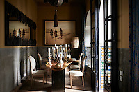 A collection of candlesticks are arranged on a dining table. A ceiling light with a tassel hangs above.