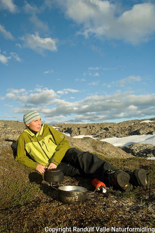 Jente slapper av i kveldssol på Saltfjellet. ---- Girl relaxing in evening sun.