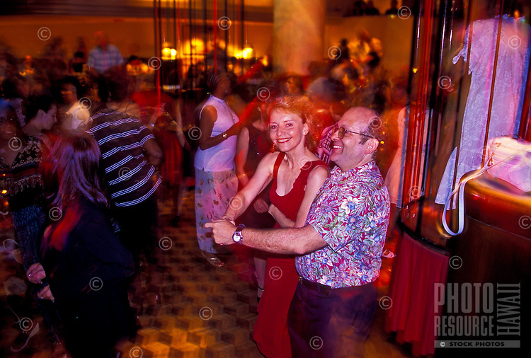 Woman in red dress and partner, swing dancing a nightclub in the Ala Moana Hotel, Waikiki, Oahu, Hawaii