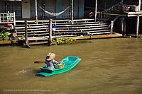 Thai woman crossing canal near Damnoen Saduak Floating Market, Damnoen Saduak, Thailand