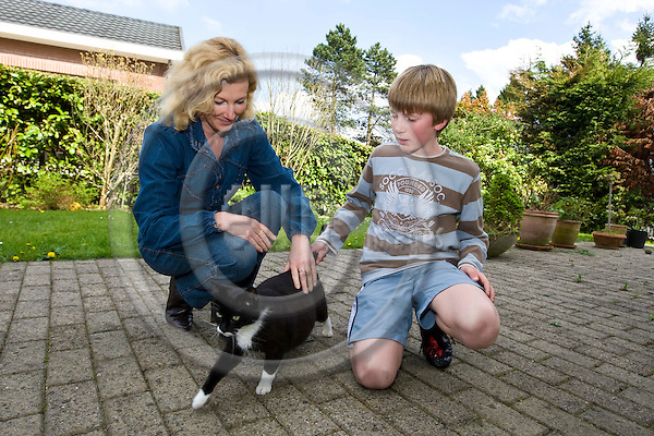 BRUSSELS - BELGIUM - 19 APRIL 2009 -- Veronique LEGROS (Ri) and her son Gaetan STRAETMANS with with a stray cat who decided to adopt the family as her new home. -- PHOTO: Juha ROININEN / EUP-IMAGES