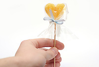 Hand with candy on stick as a Valentine present on white background