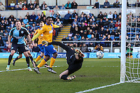 Scott Shearer of Mansfield Town (right) cannot prevent Michael Harriman of Wycombe Wanderers (not shown) from opening the scoring during the Sky Bet League 2 match between Wycombe Wanderers and Mansfield Town at Adams Park, High Wycombe, England on 25 March 2016. Photo by David Horn.