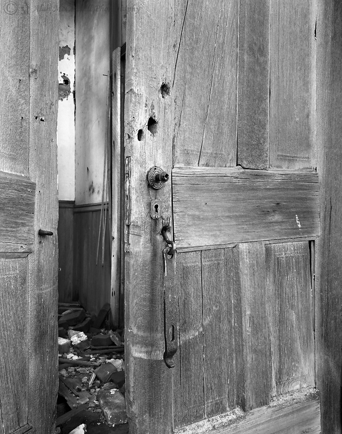 Voices of yesteryear seem to whisper beyond the doors of a Carroll County schoolhouse.  Remains of the academic structure are all that are left of a bygone time when children ran to the entrance with books held together by leather straps.  Huge wooden doors frame the entry that led to the one-room schoolhouse.  The metal latch hangs loosely from the forgotten doors, yet it left signs of daily rubbings from constant use. No longer protected from the elements, the bare wood is cracked and dry.  Glimpses into the room show only a skeleton of what once was held so dearly by local children.