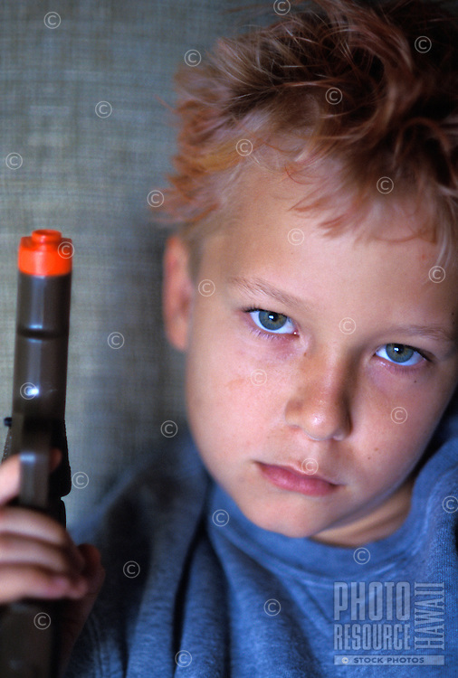 Close up portrait of a 10 year old boy with orange hair gel and play gun
