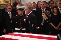 Former President George W. Bush walks past his father's casket with his wife former first lady Laura Bush during services for former President George H.W. Bush in the U.S. Capitol Rotunda in Washington, U.S., December 3, 2018. <br /> CAP/MPI/RS<br /> &copy;RS/MPI/Capital Pictures