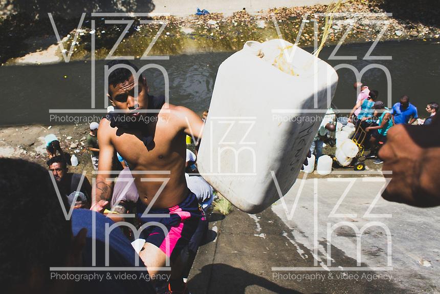 SAN AGUSTIN - VENEZUELA, 11-03-2019:  Habitantes de San Agustín tuvieron que acudir a los desagües del río Guaire para abastecerse de agua ante la creciente escasez tras el apagón en Venezuela. Otros decidieron trancar las calles y protestar hasta que les llevaron cisternas durante el 4° día de apagón que afectó Caracas y 22 estados de Venezuela debido a un fallo en Guri (Estado de Bolívar), una de las mayores represas de generación de energía eléctrica en América Latina, solo superada por la de Itaipú (entre Brasil y Paraguay). / Residents of San Agustín had to go to the drains of the Guaire River to supply themselves with water in the face of the growing shortage after the blackout in Venezuela. Others decided to block the streets and protest until they brought them cisterns during the 4th day of electricity power outage that affected Caracas and 22 states of Venezuela due to a failure in Guri (State of Bolívar), one of the largest electric power generation dams in Latin America, second only to that of Itaipú ( between Brazil and Paraguay). Photo: VizzorImage / Carolain Caraballo / Cont