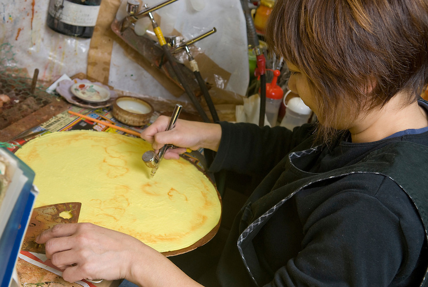 Using an air brush to paint a plastic crepe at Maiduru Corporation, Tokyo, Japan, 22nd December 2008. Maiduru corporation makes highly realistic plastic food for display in restaurant and cafe windows. .