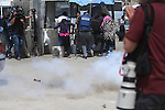 Palestinian journalists run for cover from a tear gas canister fired by Israeli security forces at the Qalandia checkpoint, between Jerusalem and Ramallah in the Israeli occupied West Bank, after two Palestinians were shot as they approached security at the border carrying a knife, police said, on April 27, 2016. Photo by Shadi Hatem
