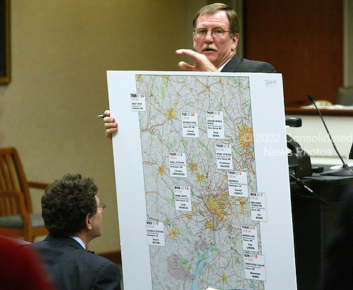 Prince William County (Virginia) Assistant Commonwealth Attorney Richard A. Conway holds a map of the Washington, DC area with the locations of the sniper shootings as defense attorney Jonathan Shapiro, seated left, looks on during the trial of sniper suspect John Allen Muhammad in Virginia Beach Circuit Court in Virginia Beach, Virginia on November 9, 2003. <br /> Credit: Tracy Woodward - Pool via CNP