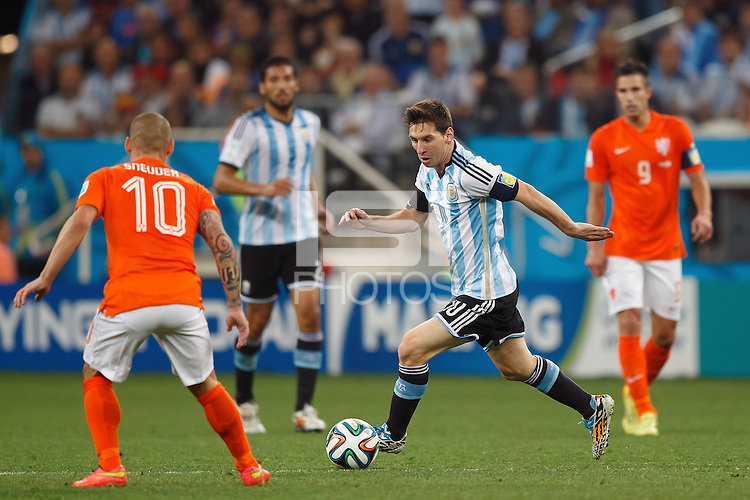 Lionel Messi of Argentina takes on Wesley Sneijder and Robin van Persie of the Netherlands
