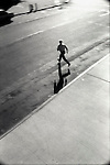 Man running across city street.