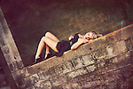 Close up of young woman with blonde hair wearing a black party dress lying on a brick wall