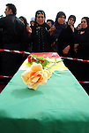 CHAMCHAMAL, IRAQ: A woman prays over a child's coffin during the funeral ceremony of 104 Kurds discovered in a mass grave...On April 15, 2010, Iraqi Kurds held a ceremony to honor the 102 children and 2 pregnant women discovered in a mass grave near the town of Dibis.  They are believed to have been killed in the 1988 Anfal genocidal campaign against Iraq's Kurds.