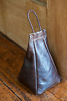 As well as handbags Matt and Jax Fothergill also design accessories such as this leather doorstop, photographed against the floorboards of the master bedroom