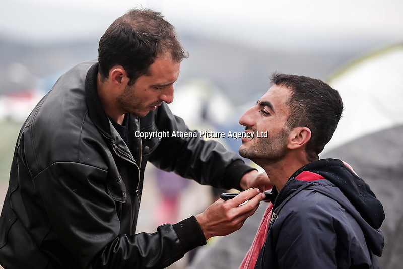 Pictured: A man helps a relative shave at the camp Monday 07 March 2016<br /> Re: Refugees at the Greek FYRO Macedonian border in Idomeni, Greece.