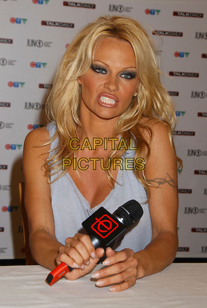 PAMELA ANDERSON.The 35th Annual JUNO Awards Press conference with host Pamela Anderson held at the Delta Halifax, Halifax, Nova Scotia, Canada..April 1st, 2006.Photo: Laura Farr/AdMedia/Capital Pictures.Ref: LF/ADM.half length microphone funny face.www.capitalpictures.com.sales@capitalpictures.com.© Capital Pictures.