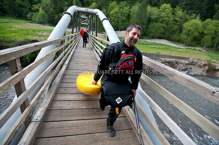 5/18/2009--Sandy, OR, USA..Kayakers Paul Kuthe (front: black helmet, yellow kayak) and Matt Preusch (writer: red helmet, orange kayak) carry their kayaks over a bridge at a recently opened stretch of the Sandy River in Oregon. The Marmot Dam was removed from the river in 2007 allowing fish and kayakers to travel the newly opened stretch of water...©2009 Stuart Isett. All rights reserved.