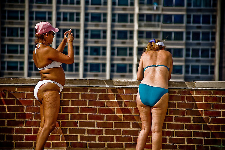 Two middle aged women wearing bikinis