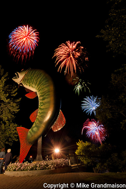 Huskie the Muskie with fireworks during the annual festival (composite image of two images taken at same place)<br /> Kenora<br /> Ontario<br /> Canada