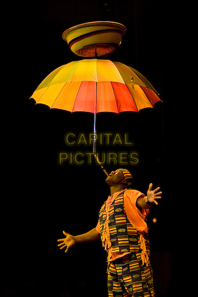 AFRIKA! AFRIKA!.Performing at The Trafford Centre, Manchester, England..July 21st, 20008.stage live performance africa balancing umbrella chin looking up juggling pot pottery vase.CAP/AT.© Alan Towse/Capital Pictures.