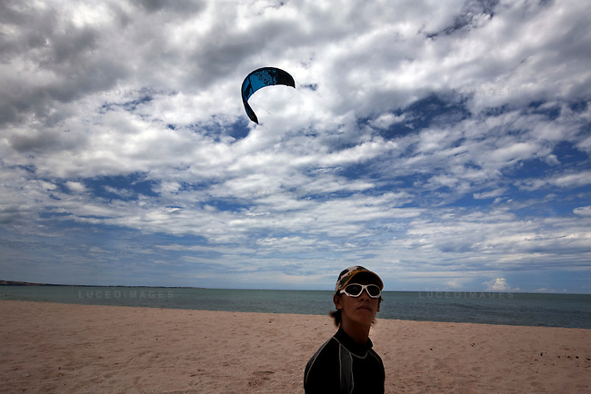 Binh, an employee at STORM Kiteboarding, watches as the first kite of the day launches into the air.