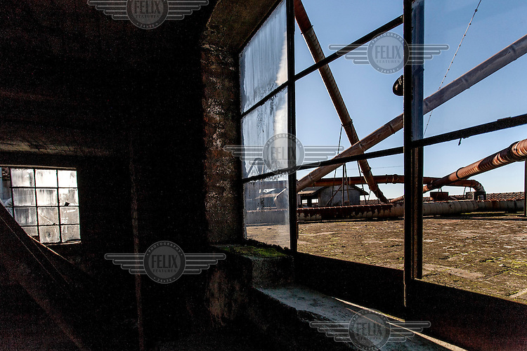 A view through a window at the abandoned Robinson cork factory. The factory was founded in 1840 and stayed in production till 2009, at which time it was still partially powered by steam energy. At its peak the company employed 2000 labourers and cork is still Portugal's most important export product. /Felix Features