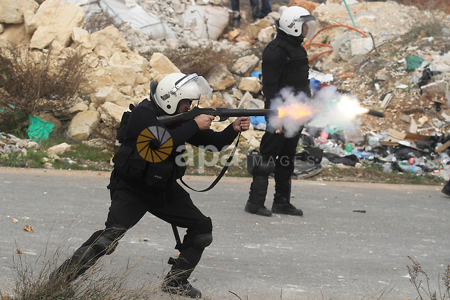 A Palestinian police officer fires a tear gas canister towards protesting youth from the Palestinian refugee camp of al-Jalazoun refugee camp near the West Bank city of Ramallah January 12, 2014. At least 50 people were hurt on Sunday in a clash between Palestinian police and residents of the refugee camp protesting against a strike in a U.N. aid agency that has paralysed services, police and an ambulance service said. The demonstration was the most violent in a series of protests stemming from a strike for higher pay by local employees of the United Nations Relief and Works Agency (UNRWA). Photo by Issam Rimawi
