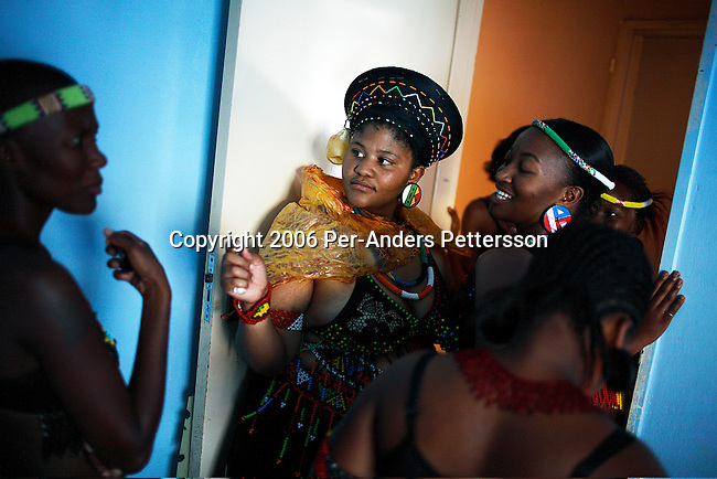 SOWETO, SOUTH AFRICA DECEMBER 16: Nondumiso Rakale (c) age 21, chats to her friends as she goes through a coming of age ceremony outside her house on December 16, 2006 in Jabulani section of Soweto, Johannesburg, South Africa. She is now seen as a grown woman and she can date men. A cow was slaughtered a day earlier, and all the part of the animal is used in the ceremony. She wears a dried cow skin on her back. Relatives and friends donated money and put it in her hat. Many people fight to keep their old traditions as they are facing difficulties to keep them, because of the life is becoming more westernized. Soweto is South Africa?s largest township and it was founded about one hundred years to make housing available for black people south west of downtown Johannesburg. The estimated population is between 2-3 million. Many key events during the Apartheid struggle unfolded here, and the most known is the student uprisings in June 1976, where thousands of students took to the streets to protest after being forced to study the Afrikaans language at school. Soweto today is a mix of old housing and newly constructed townhouses. A new hungry black middle-class is growing steadily. Many residents work in Johannesburg but the last years many shopping malls have been built, and people are starting to spend their money in Soweto.  .(Photo by Per-Anders Pettersson/Getty Images)..