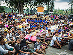 13 JULY 2016 - UBUD, BALI, INDONESIA: People gather on the plaza in front of the local temple with the remains of their family members during the mass cremation Wednesday. Local people in Ubud exhumed the remains of family members and burned their remains in a mass cremation ceremony Wednesday. Almost 100 people will be cremated and laid to rest in the largest mass cremation in Bali in years this week. Most of the people on Bali are Hindus. Traditional cremations in Bali are very expensive, so communities usually hold one mass cremation approximately every five years. The cremation in Ubud will conclude Saturday, with a large community ceremony.       PHOTO BY JACK KURTZ