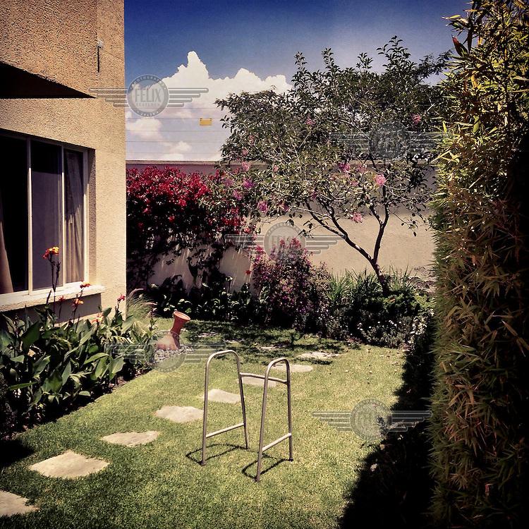 Grandma Angelina's walking frame stands alone in a garden in Cumbaya.