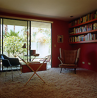 The red-walled study is filled with classic period pieces of furniture such as the Eames DAX chair and the floor is covered in shag-pile carpet