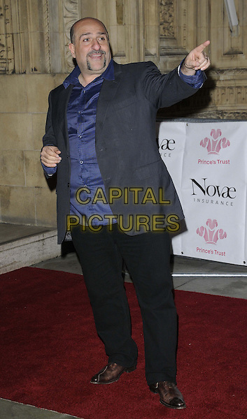 Omid Djalili.The 'We Are Most Amused' Prince's Trust Comedy Gala, Royal Albert Hall, Kensington Gore, London, England..28th November 2012.full length blue shirt grey gray suit jacket handlebar moustache mustache facial hair black trousers hand arm finger pointing .CAP/CAN.©Can Nguyen/Capital Pictures.
